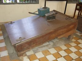 Waterboard. Prisoners' legs were shackled to the bar on the right, their wrists were restrained to the brackets on the left and water was poured over their face using the blue watering can.