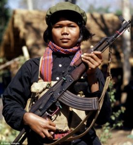 A female Khmer Rouge fighter or 'mit naree' carries an AK-47 assault rifle, a weapon of Communist revolution the world over.