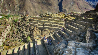The mountainsides of Ollantaytambo, Peru are covered by an extensive set of agricultural terraces which start at the bottom of the valleys and climb up the surrounding hills. The terraces permitted farming on otherwise unusable terrain; they also allowed the Incas to take advantage of the different ecological zones created by variations in altitude. Land inside the terrace is protected from the wind by lateral walls which also absorb solar radiation during the day and release it during the night; this creates a microclimate zone 2 to 3°C warmer than the ground above it. These conditions allowed the Incas to grow species of plants native to lower altitudes that otherwise could not have flourished at this site. (Ollantaytambo, Peru, 2016.)