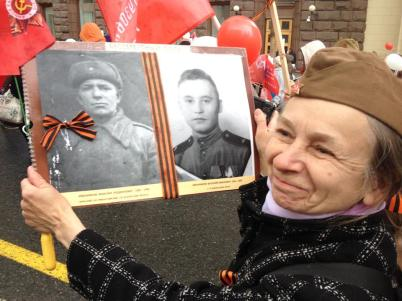 A woman proudly displays photos of relatives who served in the war - in Putin's Russia, the memory of the Great Patriotic War has been revived and reinvigorated, a king of 4th of July, Thanksgiving, and Veteran's Day rolled into one. (Moscow, Russia, 2017.)