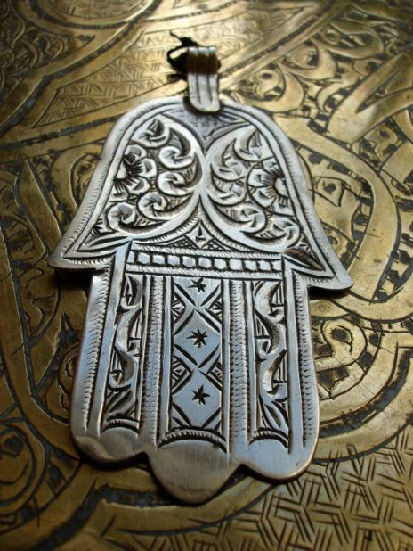 The hamsa (Berber: ⵜⴰⴼⵓⵙⵜ tafust) is a palm-shaped amulet popular throughout the Middle East and North Africa and commonly used in jewelry and wall hangings. Depicting the open right hand, an image recognized and used as a sign of protection in many times throughout history, the hamsa is believed by some, predominantly Muslims and Jews, to provide defense against the evil eye. It has been theorized that its origins lie in Ancient Egypt or Carthage (modern-day Tunisia) and may have been associated with the Goddess Tanit. The Hamsa is also known as the Hand of Fatima after the daughter of the prophet Muhammad.