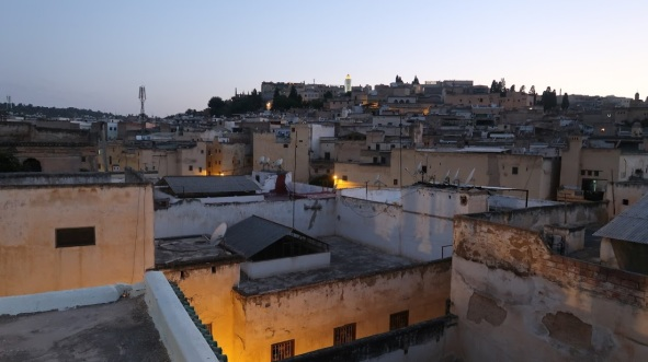 Dusk falls on the densely packed medina of Fez. In this rooftop photo, it is easy to see the density, the open courtyards, and the mosques - recognizable from their tall towers - stretching into the distance.