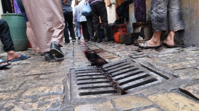 The crowded street of the medina in Fez. The ditch is in the center of the street, channeling water away from buildings and allowing pedestrians to stay dry even in the rain, beneath the awnings that are common in front of homes and shops.