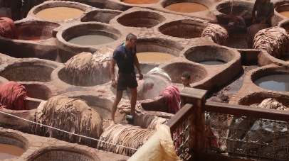 A man and his son drop animal hides - goats, cows, or camels, usually - into vats of chemicals, which dye and preserve the skins as leather.