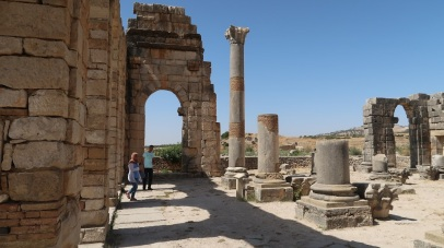 Volubilis is a partly excavated Berber city in Morocco situated near the city of Meknes, and commonly considered as the ancient capital of the kingdom of Mauretania. Built in a fertile agricultural area, it developed from the 3rd century BC onward as a Berber, then proto-Carthaginian, settlement before being the capital of the kingdom of Mauretania. It grew rapidly under Roman rule from the 1st century AD onward and expanded to cover about 42 hectares (100 acres) with a 2.6 km (1.6 mi) circuit of walls. The city gained a number of major public buildings in the 2nd century, including a basilica, temple and triumphal arch. Its prosperity, which was derived principally from olive growing, prompted the construction of many fine town-houses with large mosaic floors.